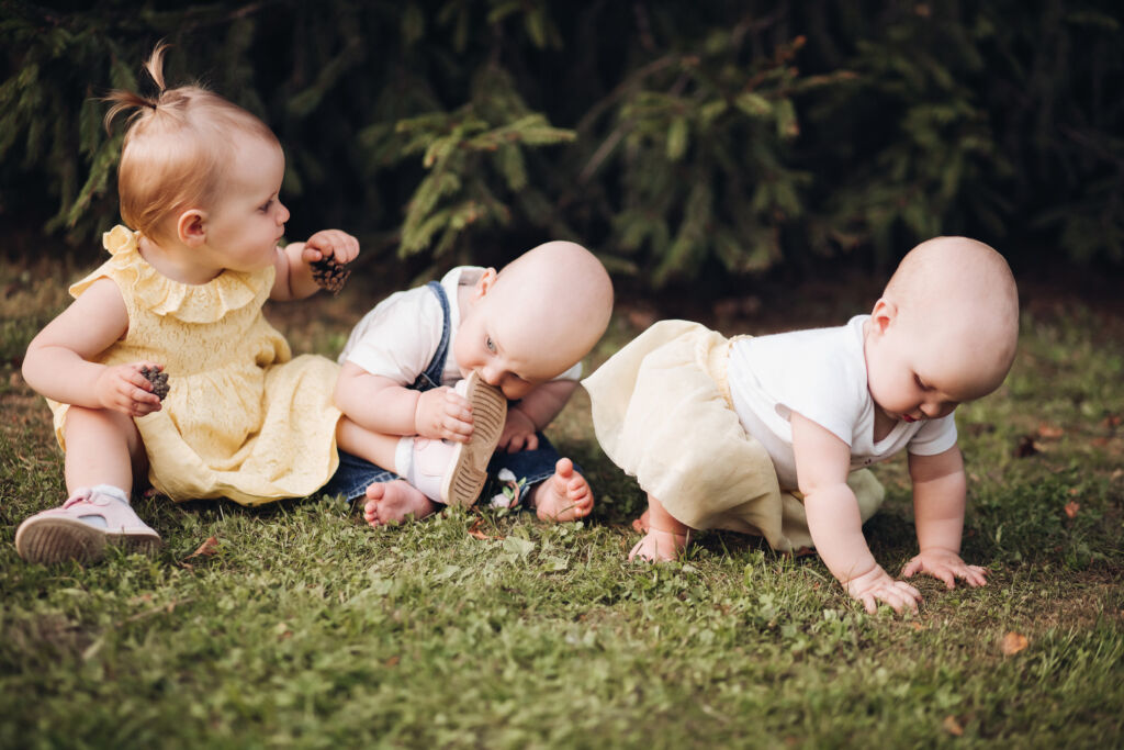 Three little children crawl on a green grass and have fun togehter