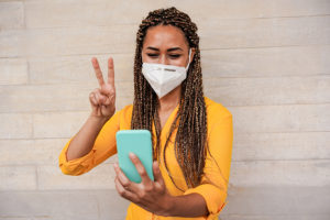 Young woman with braids doing video call while wearing face prot